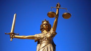 Die Statue Justitia vor einem blauen Himmel