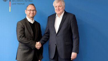 Frank Wernecke und Horst Seehofer vor der Fotowand des BMI mit gemeinsamen Handschlag