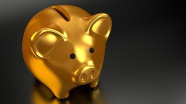 Ein vergoldetes Sparschwein vor dunklem Hintergrund.